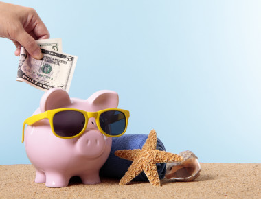 Saving for beach vacation or retirement, with pink piggy bank and sunglasses.  Studio shot with plain blue background.  Sharp focus on the five dollar bill.  Space for copy.  Warm color and directional lighting are intentional.